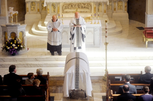 NICK SCHNELLE/JOURNAL STAR Pastor Larry Zurek leads a funeral mass for former Peoria Fire Cheief Ernie Russell on Friday morning at Sacred Heart Catholic Church. Russell was 74.